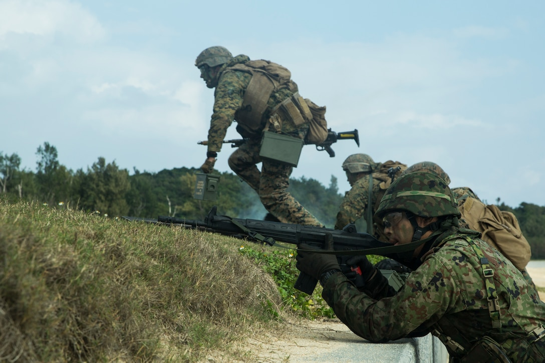 Marines with Charlie Company, Battalion Landing Team, 1st Battalion 5th Marines, 31st Marine Expeditionary Unit, and Japanese Amphibious Rapid Deployment Brigade service members maneuver toward the objective during a simulated bilateral small-boat raid on Kin Blue, Okinawa, Japan, Feb. 9.