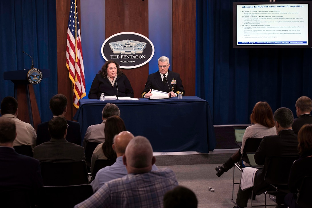 Two people, one civilian and one military, sit behind a desk and talk to reporters.