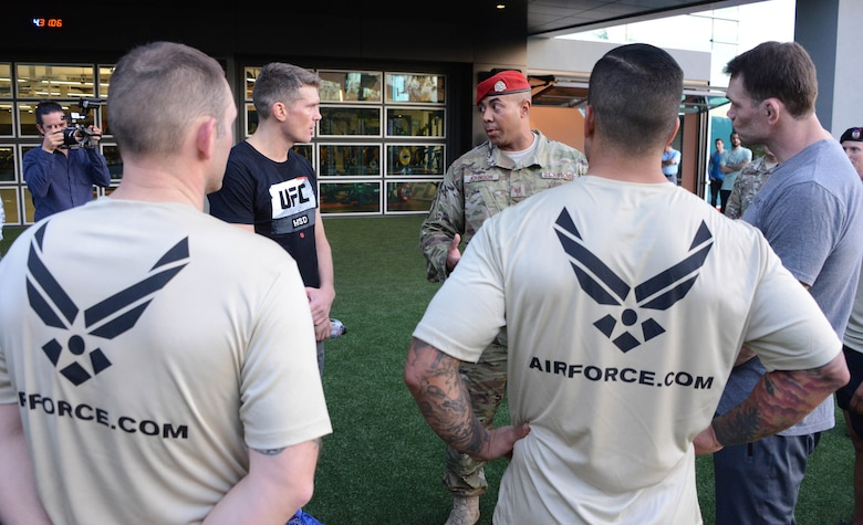 Tech. Sgt. Will Johnson, 330th Recruiting Squadron, gives instructions on how to perform special warfare memorial push-ups to Ultimate Fighting Championship fighters Forrest Griffin and Stephen Thompson during a production at the UFC Performance Institute in Las Vegas,
