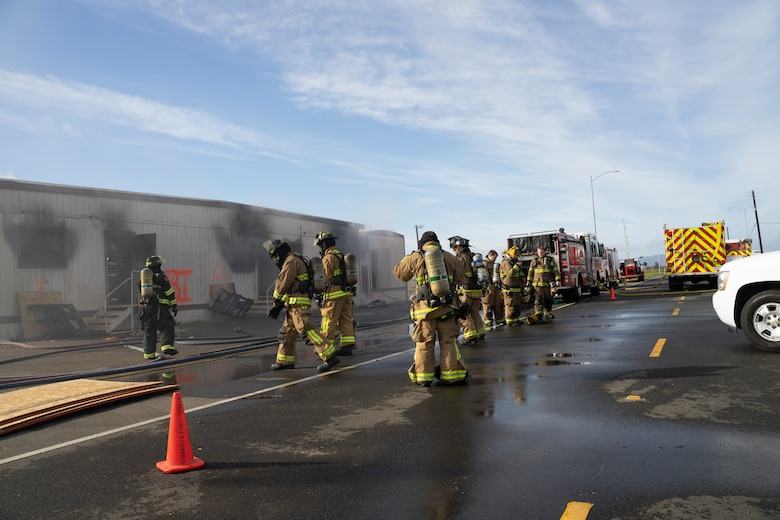 Firefighters from various local fire emergency services participate in a live burn training at Travis Air Force Base, California, Jan. 14, 2020. Travis Fire Emergency services and 10 other fire departments used four buildings at Travis AFB for live-fire training before conducting a final controlled burn to remove them. (Courtesy photo)