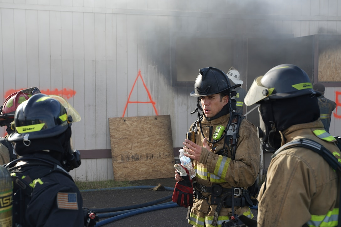 Arturo Perez, center, San Ramon Valley Fire Department instructor, instructs Airmen from the 60th Civil Engineer Squadron during a live burn training at Travis Air Force Base, California, Jan. 14, 2020. Travis Fire Emergency services and 10 other fire departments used four buildings at Travis AFB for live-fire training before conducting a final controlled burn to remove them. (Courtesy photo)