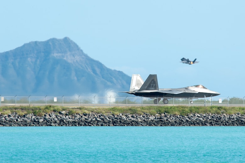A Hawaii Air National Guard F-22 Raptor taxis down the Honolulu Airport Runway Jan. 29, 2020, as an F-35A Lightning II takes off.
