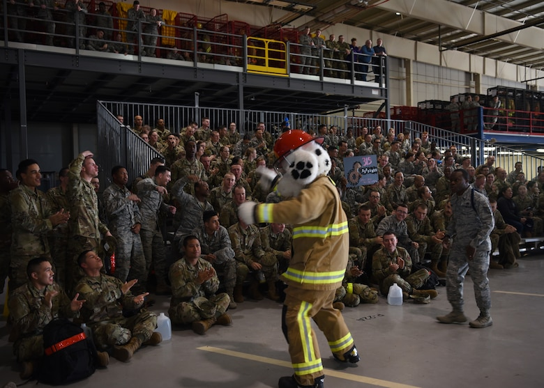 Sparky, National Fire Protection Association mascot, and U.S. Air Force Tech. Sgt. Derwin Finley, 312th Training Squadron military training leader, work together to amp up the attendees before the 17th Training Group Drill Competition inside the Louis F. Garland Department of Defense Fire Academy High Bay on Goodfellow Air Force Base, Texas, Feb. 7, 2020. Many agencies on base have mascots, which make appearances during special events to promote team unity and morale. (U.S. Air Force photo by Airman 1st Class Abbey Rieves)