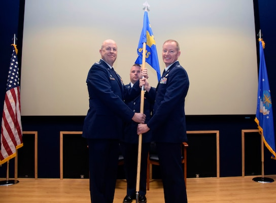 """Col. James C. """"JC"""" Miller, 433rd Operations Group commander, presents the guidon to Lt. Col. Douglas P. Schoenenberger, 68th Airlift Squadron commander, during an assumption of command ceremony at Joint Base San Antonio-Lackland, Texas, Feb. 8, 2020."""