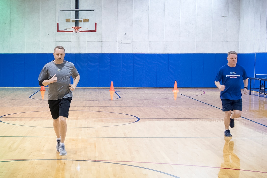 To the left, Master Sgt. Wesley Fletcher, 434th Aircraft Maintenance Squadron specialist flight chief, and Chief Master Sgt. Chad Weisend, 434th AMXS superintendent perform the new Air Force high aerobic multi-shuttle run. The 20 meter HAMR has the same correlation to predict V02 aerobic capacity as the 1.5-mile run, while also matching the age and gender scoring requirements. (U.S. Air Force photo/Master Sgt. Ben Mota)