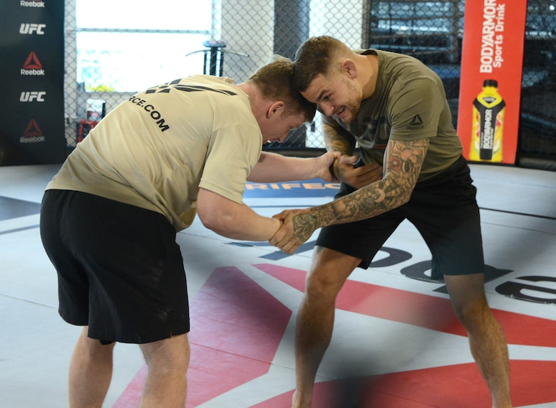 Ultimate Fighting Championship fighter Dustin Poirier conducts some grappling moves with a special warfare Airman as part of a production at the UFC Performance Institute in Las Vegas, Nevada.