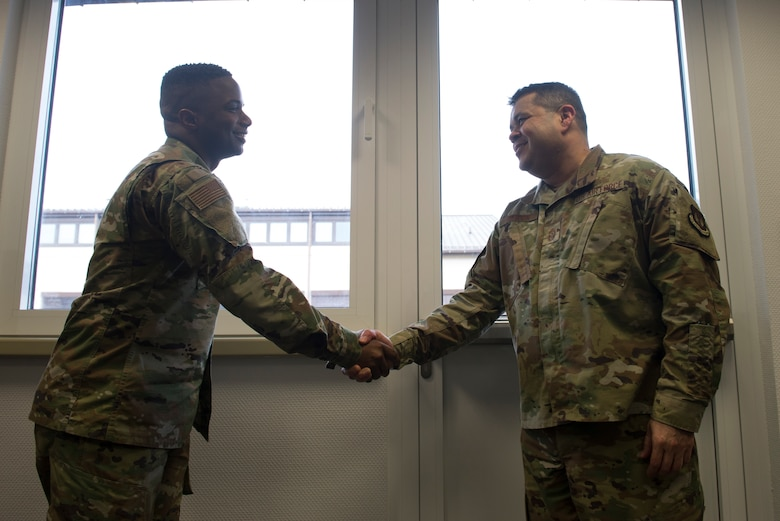 U.S. Air Force Chief Master Sgt. Ernesto Rendon, 86th Airlift Wing command chief, right, coins Tech. Sgt. Marcus Bias, 86th AW equal opportunity specialist, at Ramstein Air Base, Germany, Jan. 30, 2020. Together, Bias and his team of instructors executed 145 classes, resulting in an equal opportunity complaint reduction of 35 percent.