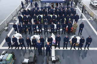 Coast Guardsmen assemble before preparing bails of cocaine to be offloaded from the Coast Guard Cutter Munro.