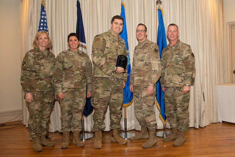 Airmen on a stage pose for a photo with award