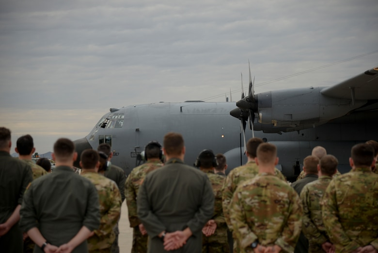 Airmen stand in formation next to an EC-130H