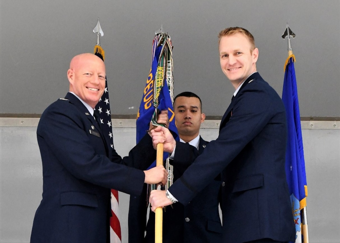 Col. Todd Tobergte, 926th Operations Group commander, hands the 706th Fighter Squadron guidon to Lt. Col. Michael Fisher, 706th FS commander, during a change of command ceremony held Jan. 31, 2020, at Nellis Air Force Base, Nev. The 706th FS seamlessly integrates Reserve personnel into the United States Air Force Warfare Center's test and training mission.