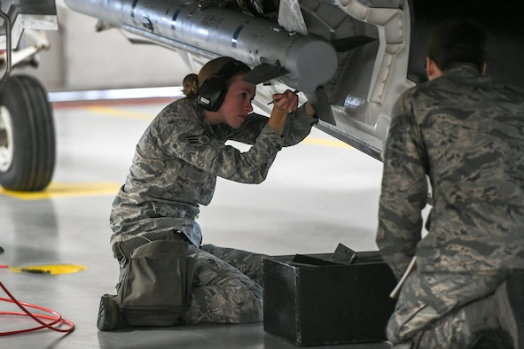Airman attaches stabilization fins onto an AIM-120 Advanced Medium-Range Air-to-Air Missile