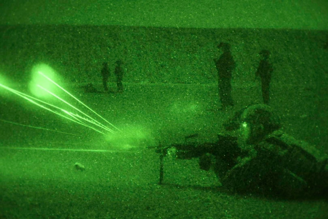 A soldier seen in a green light fires a weapon.