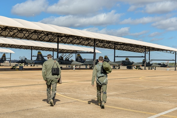 Two pilots from the 49th Fighter Training Squadron walk toward a fleet of T-38 Talons Feb. 7, 2020, at Columbus Air Force Base, Miss. The pilots were participants in exercise Southern Strike, a joint force exercise hosted by the Mississippi Air National Guard. (U.S. Air Force photo by Airman Davis Donaldson)