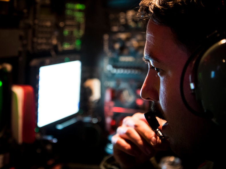 A U.S. Air Force weapon systems officer assigned to the 96th Bomb Squadron communicates with the other aircrew of a B-52H Stratofortress during Bomber Task Force Europe 20-1, Nov. 6, 2019 over the Barents Sea region of the Arctic Circle.  This deployment allows aircrews and support personnel to conduct theater integration and to improve bomber interoperability with joint partners and allied nations.  (U.S. Air Force photo by Airman 1st Class Duncan C. Bevan)