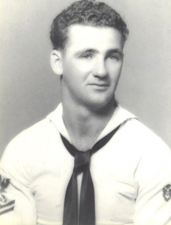 A sailor wearing a white dress uniform poses for the camera.