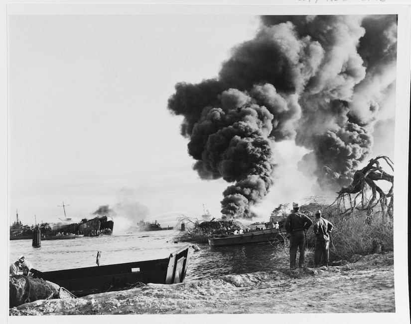 Smoke billows into the sky from two exploded ships that aren't visible as two men on the shoreline watch. Other ships seen in the distance  fight the fires.