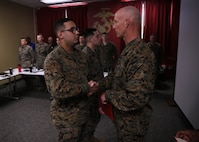 Brigadier General James F. Glynn, commanding general of Marine Corps Recruit Depot Parris Island and the Eastern Recruiting Region, right, shakes hads with Cpl. Jan FloresMartinez, an administrative specialist with 6th Marine Corps District, during an award ceremony at the 6MCD headquarters aboard MCRD Parris Island, South Carolina on Jan. 16, 2020. 6MCD Marines were awarded the Navy Achievement Medals for their outstanding devotion to their duties as administrative specialists. (U.S. Marine Corps photo by Cpl. Jack A. E. Rigsby)