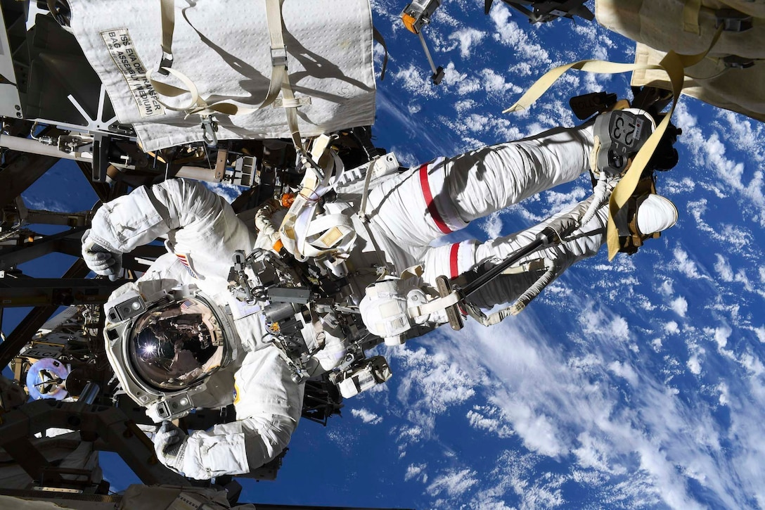 An astronaut flexes his muscles in his spacesuit while posing for a photo in space.