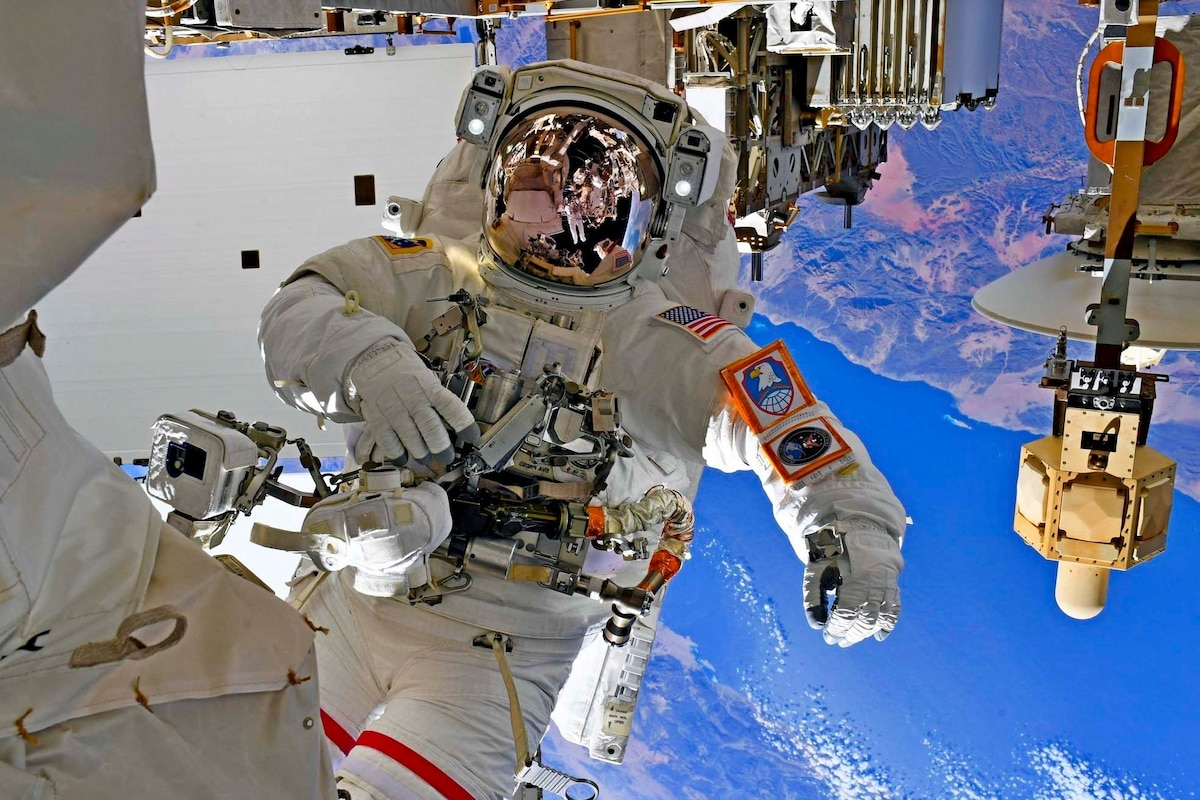 An astronaut is photographed in space, the earth visible below him.