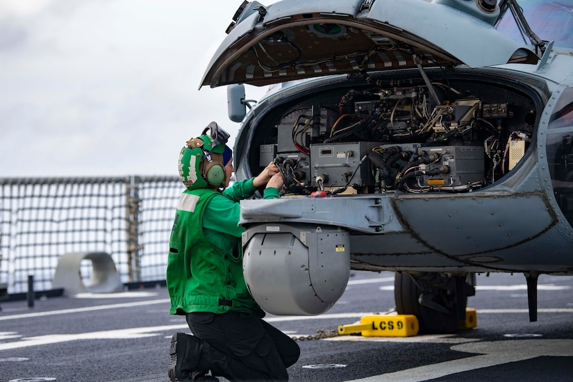 A sailor kneels on a ship's flight deck while working on an aircraft.
