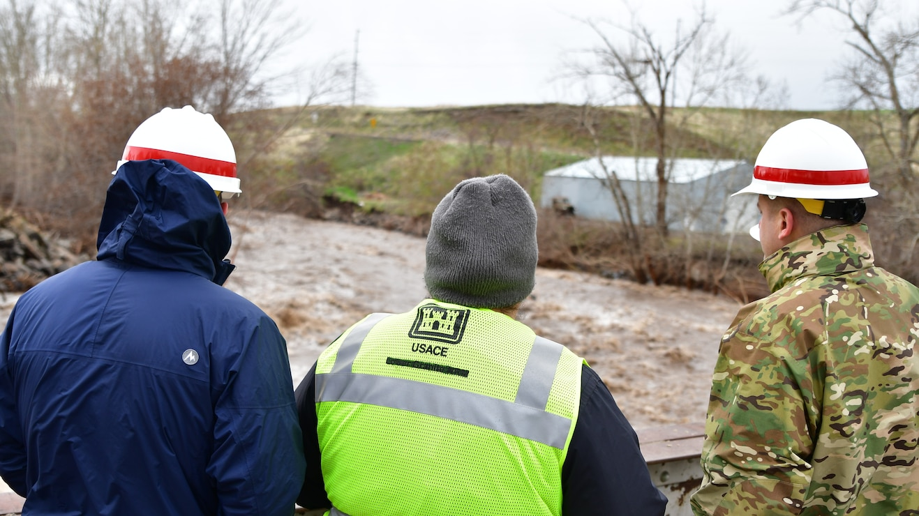 Jamie Bond, Civil Engineer of the Walla Walla Corps of Engineers, informs Lt. Col. Christian Dietz, Commander of the Walla Walla District Corps of Engineers, and Alan Feistner, Deputy District Engineer for the Walla Walla District Corps of Engineers, about water levels in the Walla Walla River in Milton Freewater.
