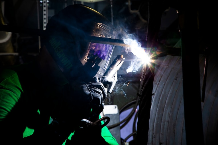 A sailor wearing protective gear welds wires.