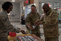 Airmen from the 354th Fighter Wing enjoy cake during the 2020 Black History Month Kickoff on Eielson Air Force Base, Alaska, Feb. 3, 2020. The council held two events during the month to celebrate African American achievements and advancements. (U.S. Air Force photo by Airman 1st Class Aaron Larue Guerrisky)