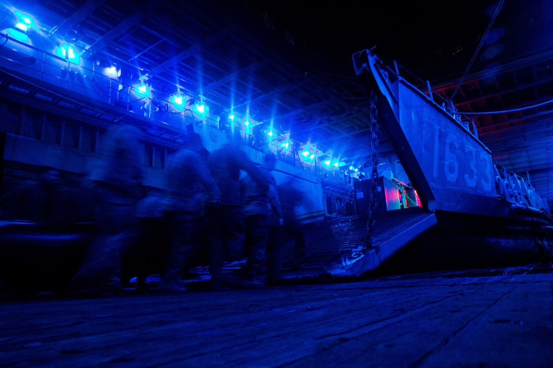 Marines, illuminated by blue light, load a boat onto a landing craft.