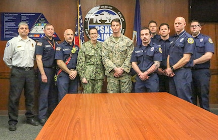 Hospital Corpsman 3rd Class Christopher S. Painter poses Captain Dianna Wolfson, commander of Puget Sound Naval Shipyard & Intermediate Maintenance Facility and with members of the Navy Region Northwest Fire & Emergency Services team after Painter received a Navy and Marine Corps Achievement Medal. Painter received the award for rendering life-saving aid to a PSNS & IMF employee Feb. 7.