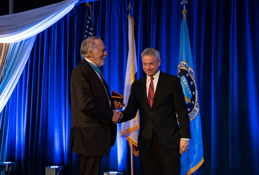 Two men in suits shake hands. One holds an award to present to the other.