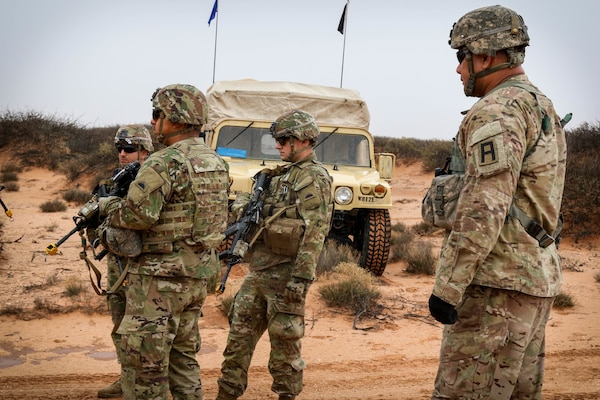 A First Army observer coach/trainer watches as Soldiers of the 2nd Battalion, 162nd Infantry Regiment, 41st Infantry Brigade Combat Team, Oregon National Guard, patrol at Fort Bliss, Texas. The patrols were created by First Army to mirror real life situations the Soldiers will face in Kosovo as part of the Kosovo Force peacekeeping mission.