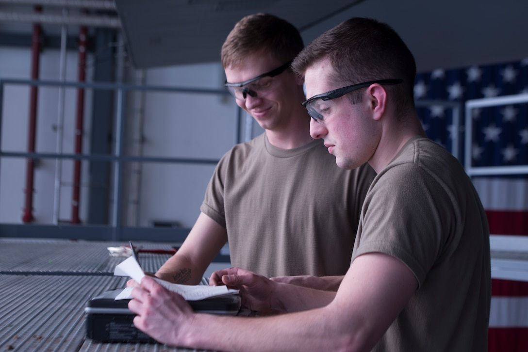 U.S. Air Force Airman 1st Class Zachary Treadwell, left, and Airman 1st Class Samuel Nemargut, 86th Maintenance Squadron aircraft structural maintenance journeymen, read instructions at Ramstein Air Base, Germany, Feb. 7, 2020. The instructions specifically list what aircraft part needs to be inspected for discrepancies and where it is located. The 86th MXS works around the clock to make sure the base's C-130's are well-maintained and ready to fly at all times.