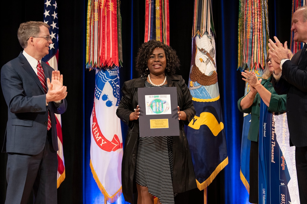 A woman stands in the center holding up a plaque; people stand on either side.