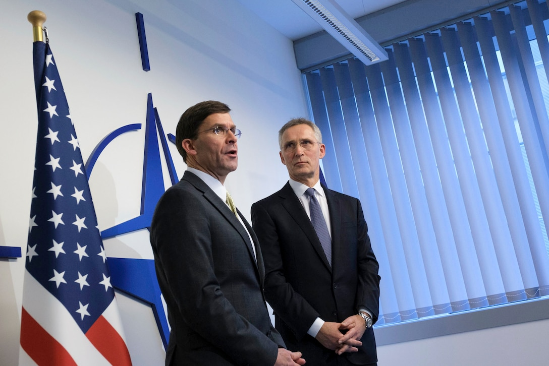 Defense Secretary Dr. Mark T. Esper speaks while standing with another official in front of a wall bearing the NATO logo.