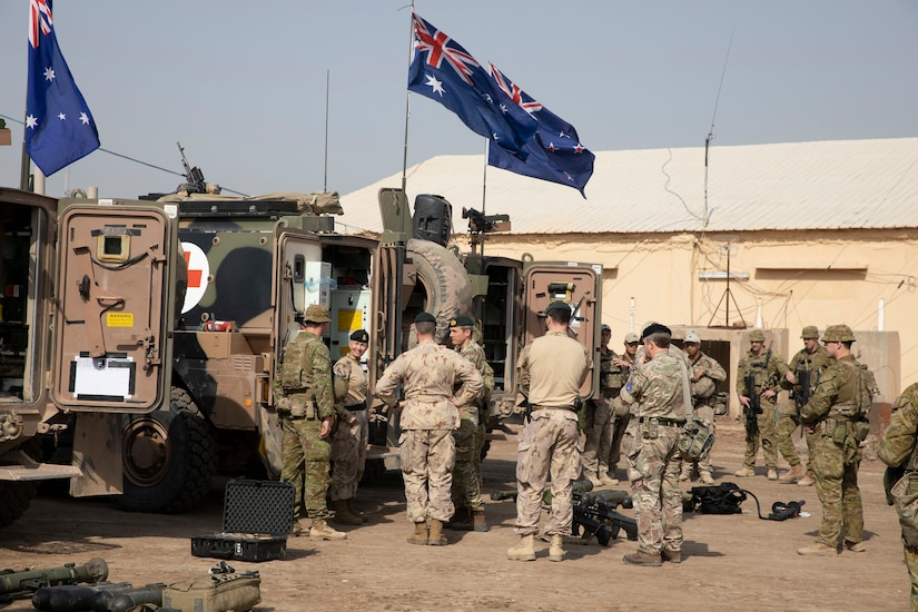 Service members stand near military vehicles.
