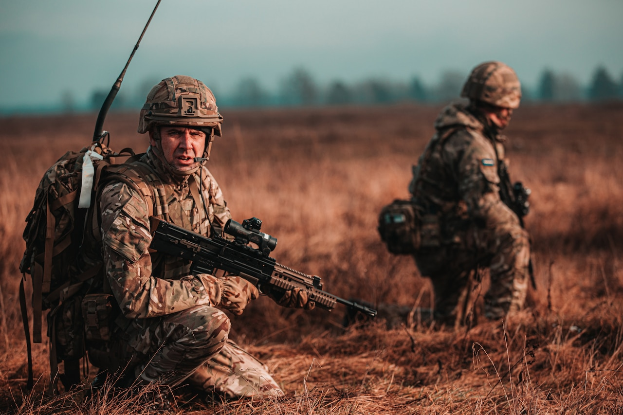 Soldiers with guns participate in a field exercise