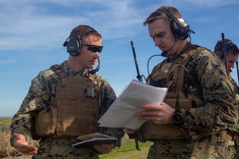 U.S. Marine Corps Master Sgt. Edwin Burch II, left, the assistant tactical air control party program manager with 1st Battalion, 10th Marine Regiment, 2nd Marine Division, and Maj. Steven Sprigg, an air officer with Headquarters Company, 2nd Marine Regiment, 2D MARDIV, coordinates a call for close air support during Exercise Fireball Eagle at Marine Corps Air Station Cherry Point, N.C., Feb. 4, 2020. The training consisted of multiple scenarios using aircraft and ground support fire to simulate real warfighting situations. (U.S. Marine Corps photo by Lance Cpl. Brian Bolin Jr.)