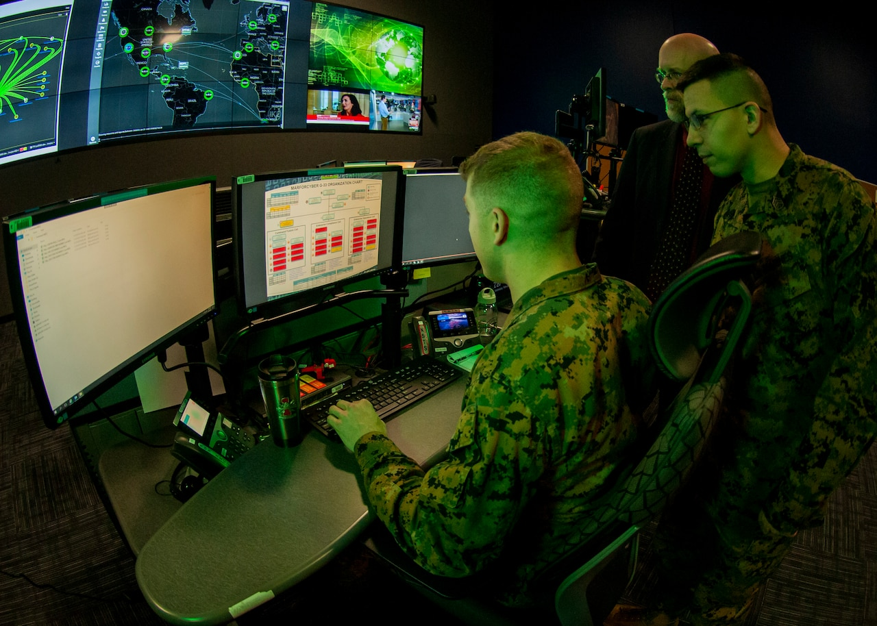 Service members looking at computer screen.