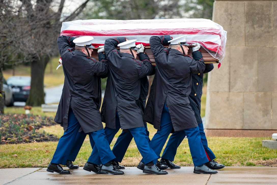 Soldiers and Marines walk in formation carrying a casket at a cemetery.