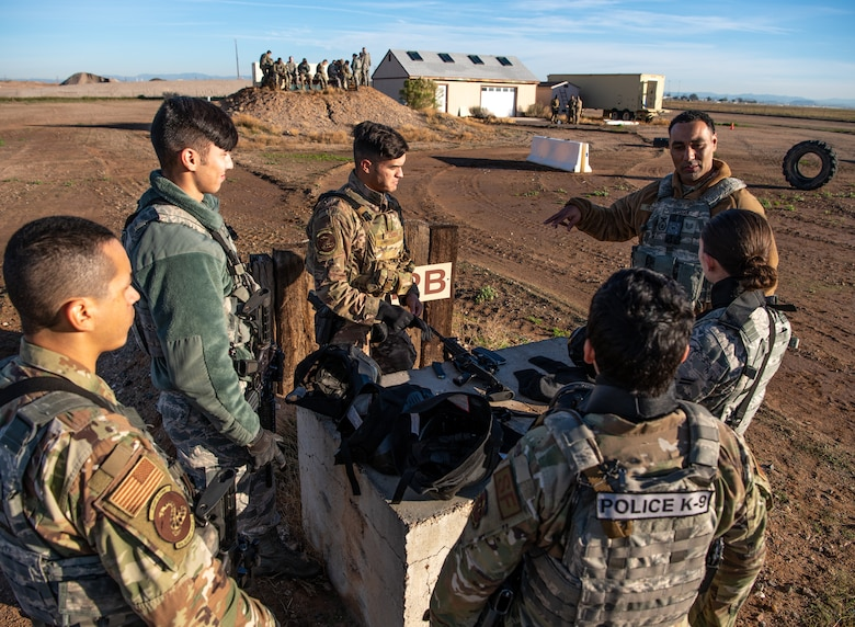 Tech. Sgt. Dominick Peterson (far right), 56th Security Forces Squadron flight instructor, briefs defenders on small unit tactics during Shoot, Move, and Communicate training Dec. 12, 2019, at Luke Air Force Base, Ariz.