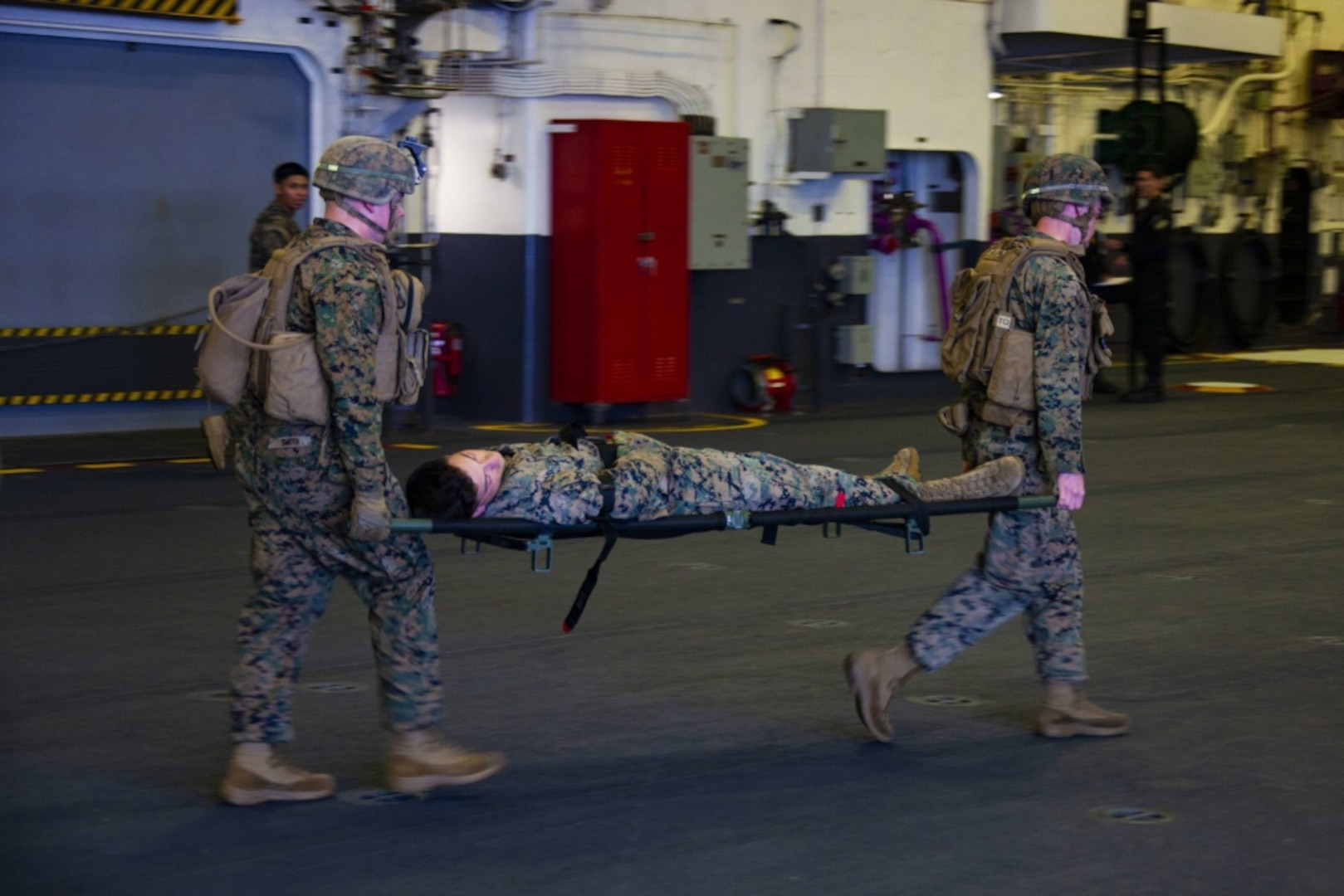 Marines with the 31st Marine Expeditionary Unit (MEU) and Sailors with the amphibious assault ship USS America (LHA 6) transport a casualty from a simulated combat zone in order to further assess his wounds during a Tactical Combat Casualty Care (TCCC) exercise
