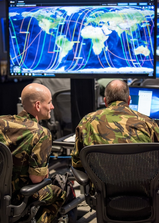 Two men in military uniforms sit looking at a monitor displaying a world map.