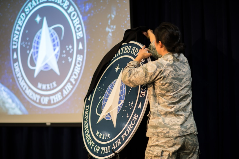 A uniformed service member pulls a black sheet off an easel that holds a circular cutout featuring the seal of the U.S. Space Force.