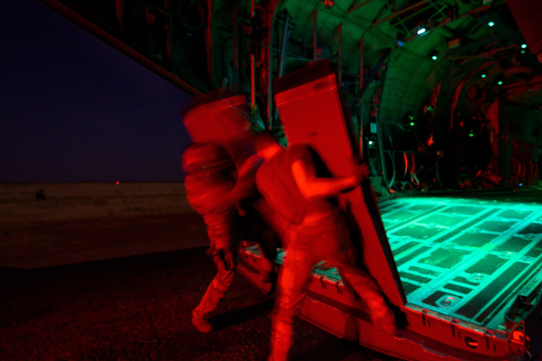 Two airmen, illuminated in red light, remove ramps from the back of an open aircraft in the dark.