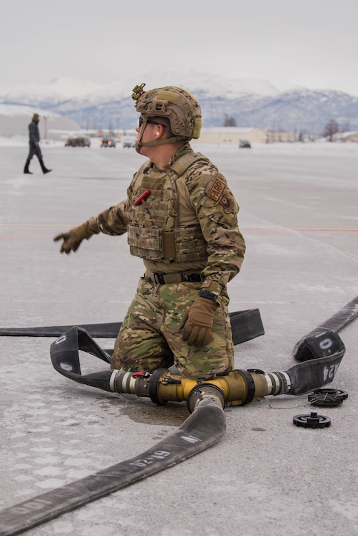 Airman 1st Class Aaron Garcia, 27th Special Operations Logistics Readiness Squadron forward area refueling point specialist, asks his teammate for assistance after connecting fuel hoses during exercise Emerald Warrior at Joint Base Elmendorf-Richardson, Alaska, Jan. 29, 2020. The main focus of Cannon's participation in Emerald Warrior was to practice refueling F-22 Raptor aircraft from a MC-130J Commando II aircraft in austere arctic conditions. (U.S. Air Force Photo by Senior Airman Marcel Williams)