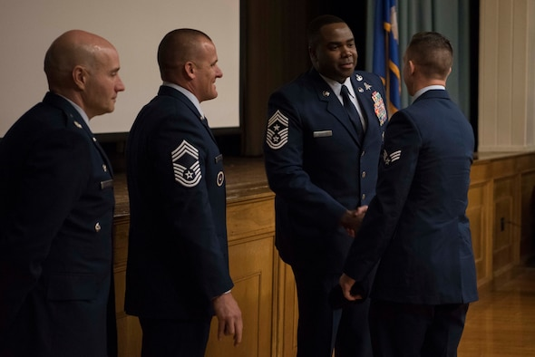 The graduation official party, including Chief Master Sgt. Robert L. Zackery III, 47th Flying Training Wing command chief master sergeant, congratulate a Tactical Air Control Party (TACP) Apprentice Course graduate at Joint Base San Antonio-Lackland, Texas, Dec. 13, 2019. Graduates were finally able to receive their black berets and blouse their dress blues after crossing the stage. (U.S. Air Force photo by Senior Airman Marco A. Gomez)