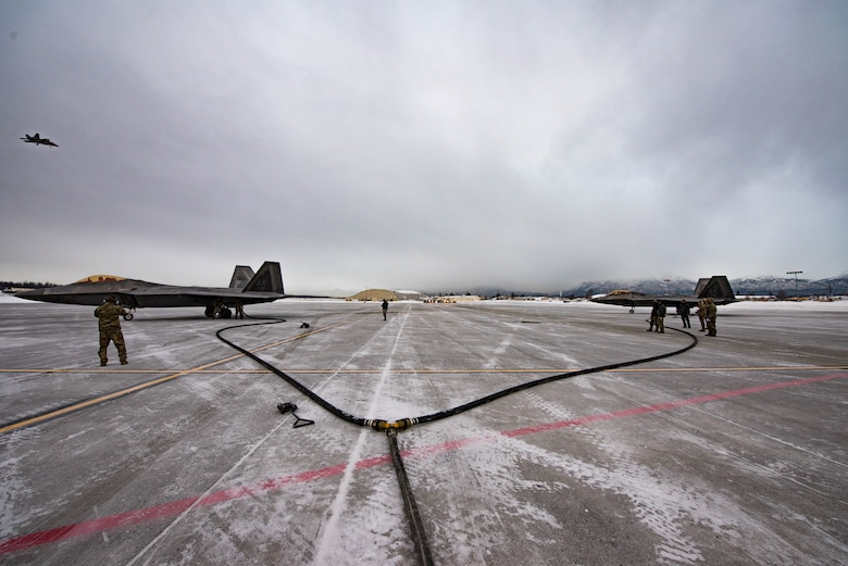 Two F-22 Raptor aircraft sit on the Joint Base Elmendorf-Richardson, Alaska, flightline while being fueled by an MC-130J Commando II aircraft during Emerald Warrior, Jan. 29, 2020. This training marked the first time FARP capabilities were tested in an arctic environment. (U.S. Air Force Photo by Senior Airman Marcel Williams)
