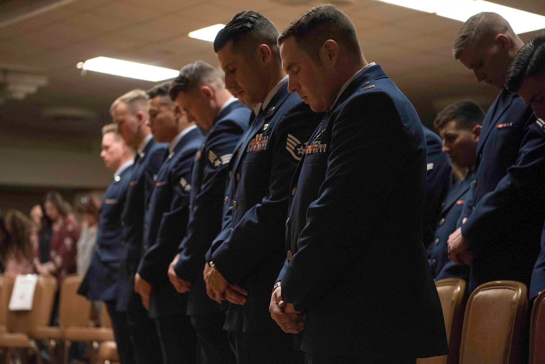 Candidates from Tactical Air Control Party (TACP) Apprentice Course Hawk 110 bow their heads in prayer during graduation at Joint Base San Antonio-Lackland, Texas, Dec. 13, 2019. Chief Master Sgt. Robert L. Zackery III, 47th Flying Training Wing command chief, was the guest speaker for class Hawk 110's graduation from TACP Apprentice Course. (U.S. Air Force photo by Senior Airman Marco A. Gomez)