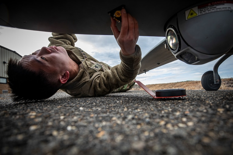 A soldier lies on the ground and checks underneath of an aircraft.